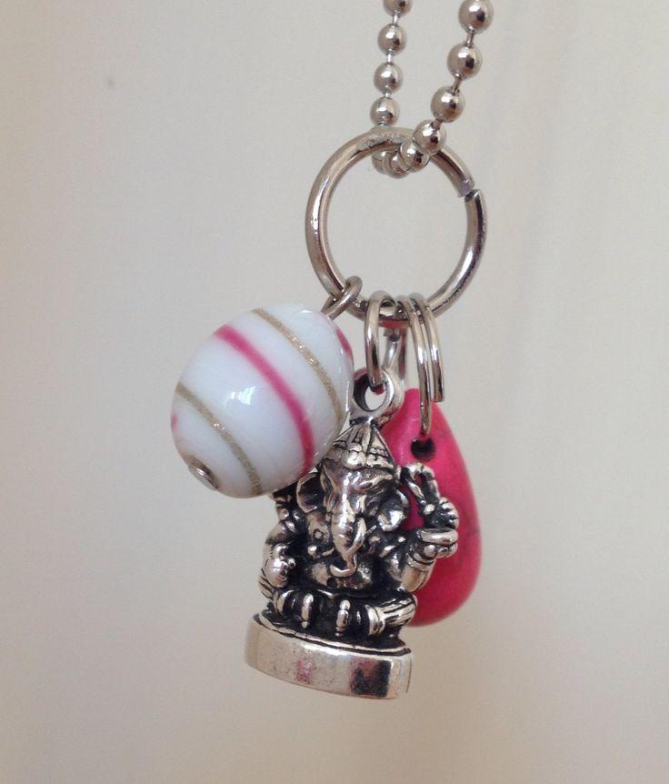 Bedel voor aan ketting met een metalen Ganesha, een roze druppel van howliet en een witte glaskraal beschilderd met roze en gouden strepen.