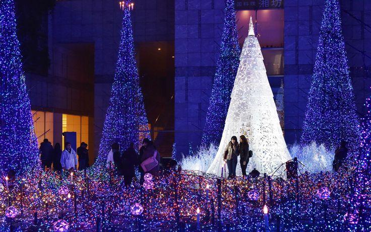 Pessoas admiram as luzes de árvores de Natal em Tóquio, no Japão, em 27 de novembro. Com o tema 'Canyon d'Azur' (Canhão Azul) a obra é iluminada por 250 mil luzes de LED e ficará em exibição até o dia 12 de janeiro