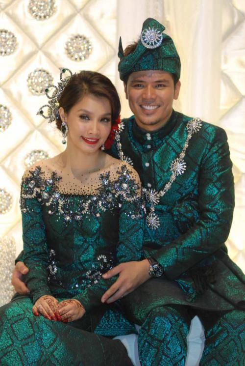 Closeup pengantin pakai songket emerald green.     Scha's makeup is simple: classic red-lipstick matches her hair accessory, which is good. Her eyes are not matched to her green outfit, she opted for a neutral eye to be paired with red lips.