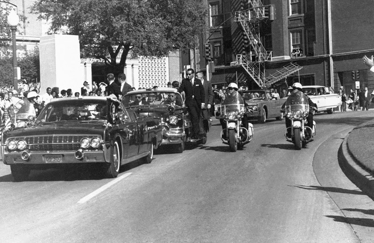 "This is the famous picture taken by Associated Press photographer  James Altgens, snapped between gunshots #2 and #3. Both of the  limo's victims (JFK and Governor John Connally) can be seen through  the car's windshield reacting to their wounds, which were sustained  just seconds earlier when bullet ""CE399"" from Lee Harvey Oswald's  rifle pierced the backs of both men."