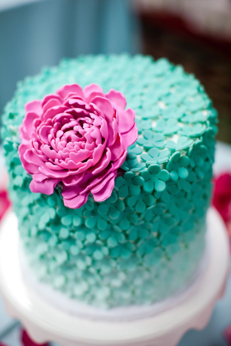 Pretty wedding cake with large pink flower and mini teal  http://www.weddingwire.com/biz/masterplan-events-silver-spring/website/5318081809195a06.html