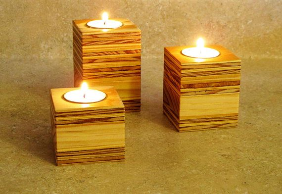 """Naturally warm with soft candle light make these wooden candle holders perfect for any space. Made from reclaimed wood harvested locally in the mid-west. The pieces are sanded, sealed with Teak oil and polished to a silky smooth finish. Each set will be completely unique. No two will look exactly the same. Who would have thought plywood would look so good!    Small size - 2 1/8"""" H x 2 3/8"""" W x 2 3/8"""" L  Medium size - 2 3/4"""" H x 2 3/8"""" W x 2 3/8"""" L  Large size - 3"""" H x 2 3/8"""" W x 2 3/8"""" L…"""