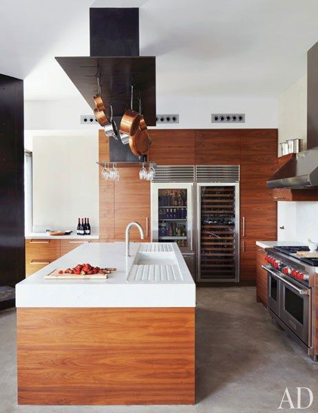 The pot rack and marble-top island in the kitchen were custom made, the refrigerator and wine storage are by Sub-Zero, and the range and hood are by Wolf.