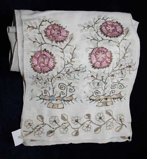 Cloth, white, cotton, decorated on both ends with embroidery and goldthread; ornate with peony flowers: beige and pink thread.