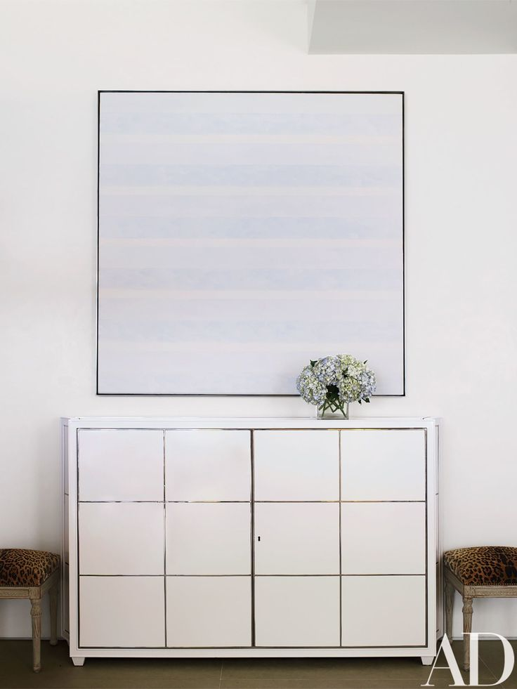On a nearby wall, Agnes Martin's Untitled #1 hangs above a custom-made lacquer-and-steel buffet that houses a television.