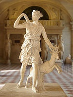 """The Diana of Versailles is a slightly over lifesize marble statue of the Greek goddess Artemis (Latin: Diana), with a deer, located in the Musée du Louvre, Paris. It is a Roman copy (1st or 2nd century AD) of a lost Greek bronze original attributed to Leochares, c. 325 BC. The statue is also known as Diana à la Biche, Diane Chasseresse (""""Diana Huntress""""), Artemis of the Chase, and Artemis with the Hind.  The statue was discovered in Italy: the Louvre website suggests Nemi."""