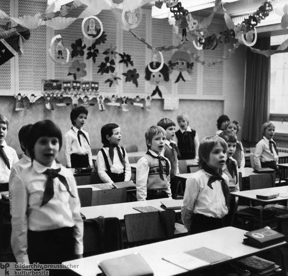 """First-Graders at a School in East Berlin (1979)-The Pioneer Organization """"Ernst Thälmann"""" (named after the former head of Germany's Communist Party [KPD] who was murdered by the Nazis) included children between the ages of 6 and 13. Pioneers in classes 1-3 were called """"Young Pioneers""""; those in classes 4-7 were called """"Thälmann Pioneers."""" The pioneer uniform included a white shirt and a colored neck-tie (blue for the Young Pioneers, red for the Thälmann Pioneers starting in December 1973)…"""
