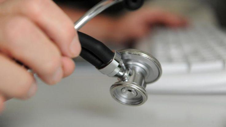 Ein Arzt aus Deizisau hält ein Stethoskop in der Hand, mit der anderen Hand bedient er eine Computertastatur