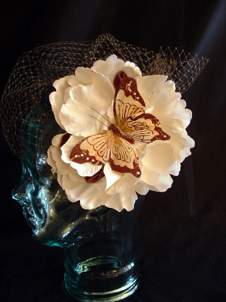 Ivory flower with veiling and painted feather butterfly.