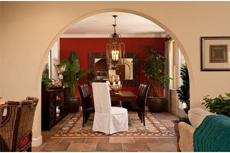 A graceful arch perfectly frames the rich red wall, rustic light fixture and mirror in this dining room from Pardee Homes, San Diego. The angled white chair invites the viewer in.