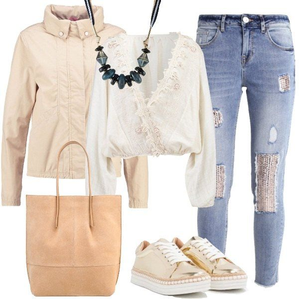 L'abbinamento jeans effetto usato con inserti in paillettes e camicetta con scollo incrociato è valorizzato da una collana importante in metallo e vetro blu notte e dalle sneakers oro e bianche. Per finire la giacca leggera e la borsa shopping color carne.