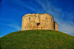 "Clifford's Tower, York, England - This photo is so misleading (but I like that)! It's right in the middle of urban city ""stuff"" and looks quite out of place."