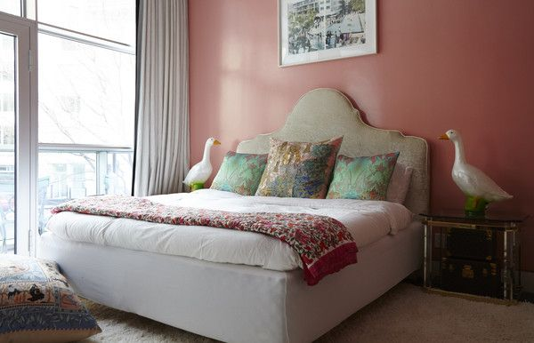 Bohemian Eclectic Bedroom: Large headboard and colorful throw pillows atop white bedding..