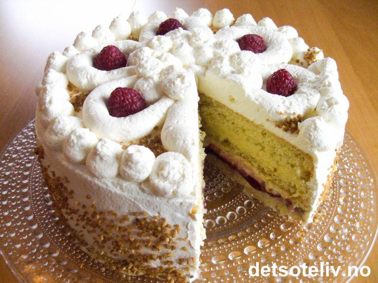 """Dette er en kake som jeg blitt spurt om oppskriften på en rekke ganger. """"Georginekake"""" består av både sukkerbrødsbunn og mandelbunn som fylles med bringebærsyltetøy og hjemmelaget vaniljekrem. Krempynten på toppen av kaken skal sprøytes som en vakker georgineblomst. I tillegg består pynten av friske, søte bringebær og krokan. Kaken er åpenbart populær og man kan lett forstå hvorfor!"""