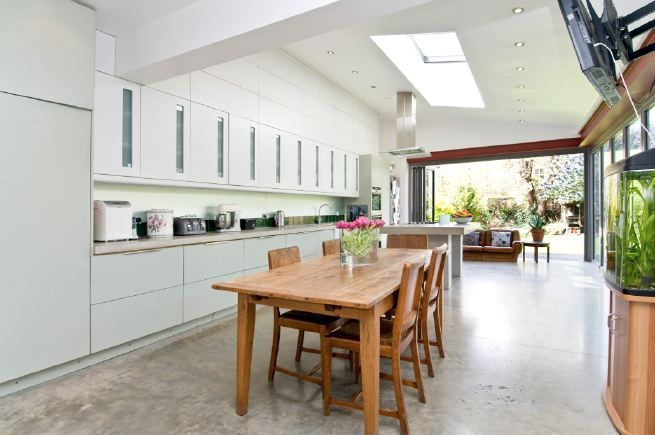 Stylish kitchen with floor to ceiling working units, levelled, polished concrete floor, pitched roof with large skylight and concrete work surfaces and central hob.