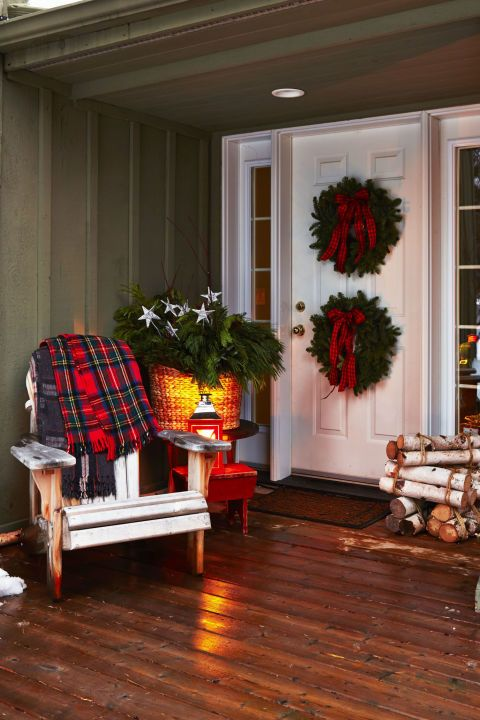 Sometimes more really is more. Double down on door decorations for twice the fun, and round out the entrance with stacked birch logs and a cozy plaid blanket. Click through for more  outdoor Christmas decorations.