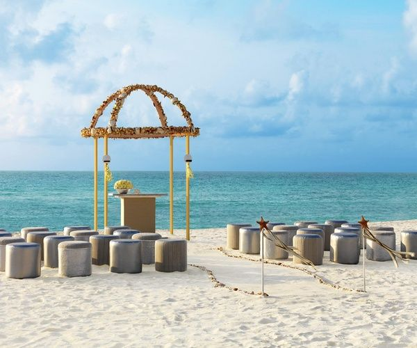 Floral canopy, fabric stools and seashell lined aisles for beach wedding ceremony | Metallic Sands Collection at Palace Resorts #destinationwedding