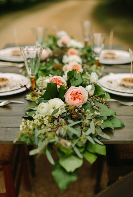 Brides.com: Unique Centerpiece Idea: Fresh Flower Runners. This simple, rustic floral runner from Soul Flowers, a Nashville-based florist, combines blush garden roses, white ranunculus, and tons of bright leaves.