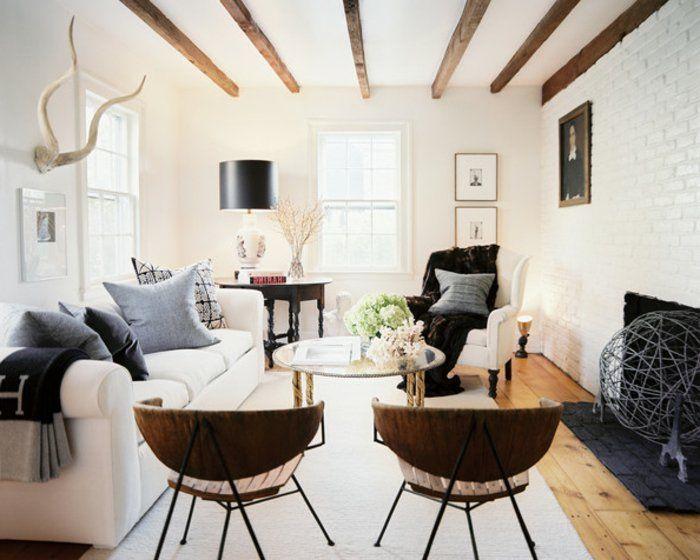deco-contemporaine-rustique-canapé-blanc-fauteuil-chaises-en-bois-et-métal-table-basse-en-verre-et-metal-tapis-blanc-cassé-cheminée-rustique-mur-en-briques-blanches-poutre-apparente-décor-en-blanc-et-bois