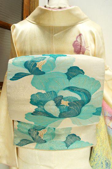 銀の地に、ターコイズブルーの階調美しく織り出された大輪の牡丹の花が印象的な袋帯です。