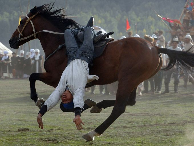 Photo taken on September 10, 2014 shows a Kyrgyz rider performing during the first World Nomad Games in the Kyrchin (Semenovskoe) gorge, some 300 km from  Bishkek. Teams of Azerbaijan, Kazakhstan, Belarus, Mongolia and Tajikistan take part in the games. AFP PHOTO / VYACHESLAV OSELEDKO        (Photo credit should read VYACHESLAV OSELEDKO/AFP/Getty Images)