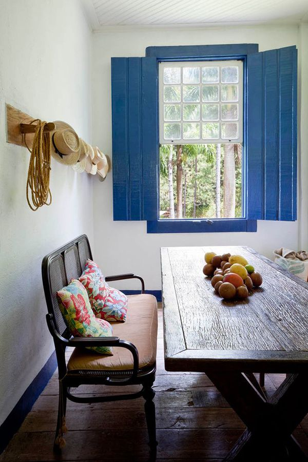"""""""Farm"""" dining room...white walls, peacock blue shutters, wood farm table, antique rattan settee, and natural wood floors."""