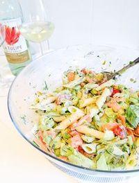 Koude pasta salade met gerookte zalm  Ingredienten voor 4 personen - 200 g penne1. – 1/2 komkommer, in blokjes – 1 bakje cherrytomaatjes, in partjes – 1 bosje lente-uitjes, kleingesneden – 15 augurken, fijngehakt – 1 potje kappertjes, fijngehakt – 1 bakje verse bieslook, fijngehakt – 1 bakje verse dille, fijngehakt – 100 g ijsbergsla – 2 citroenen, uitgeperst – 200 g gerookte zalm, in plakjes gesneden – 5 eetl dille-komkommer dressing – zout – peper
