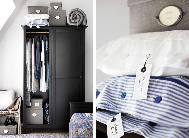 Een zwarte houten kleerkast in rustieke stijl vol kleding. Close-up van de blauw-wit gestreepte kussenslopen die erop liggen en worden gebruikt als opberger. Er hangen etiketten aan waarop staat wat erin zit.