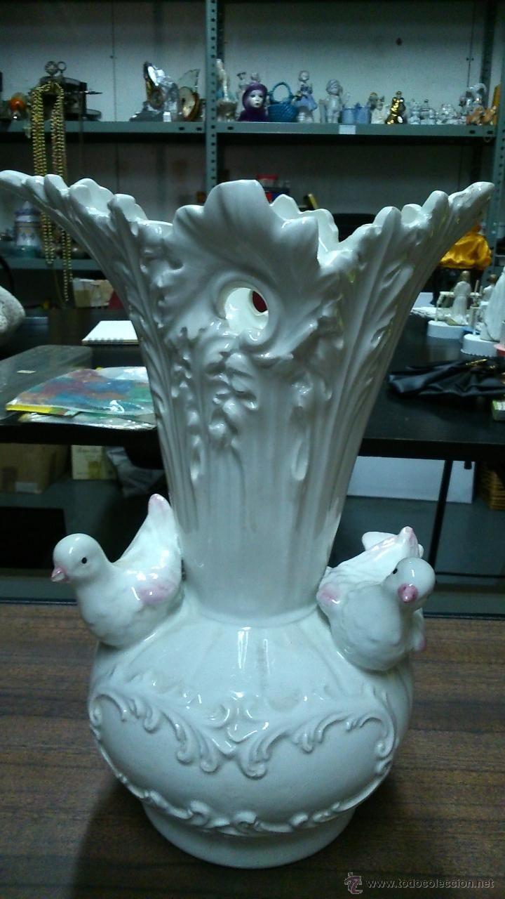 Florero blanco de `porcelana con adornos de pájaros.