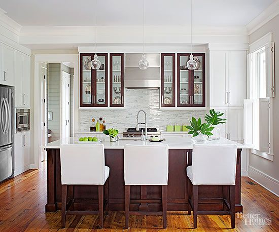 By repeating the same two colors, white and chocolate, this small kitchen feels open and bright.