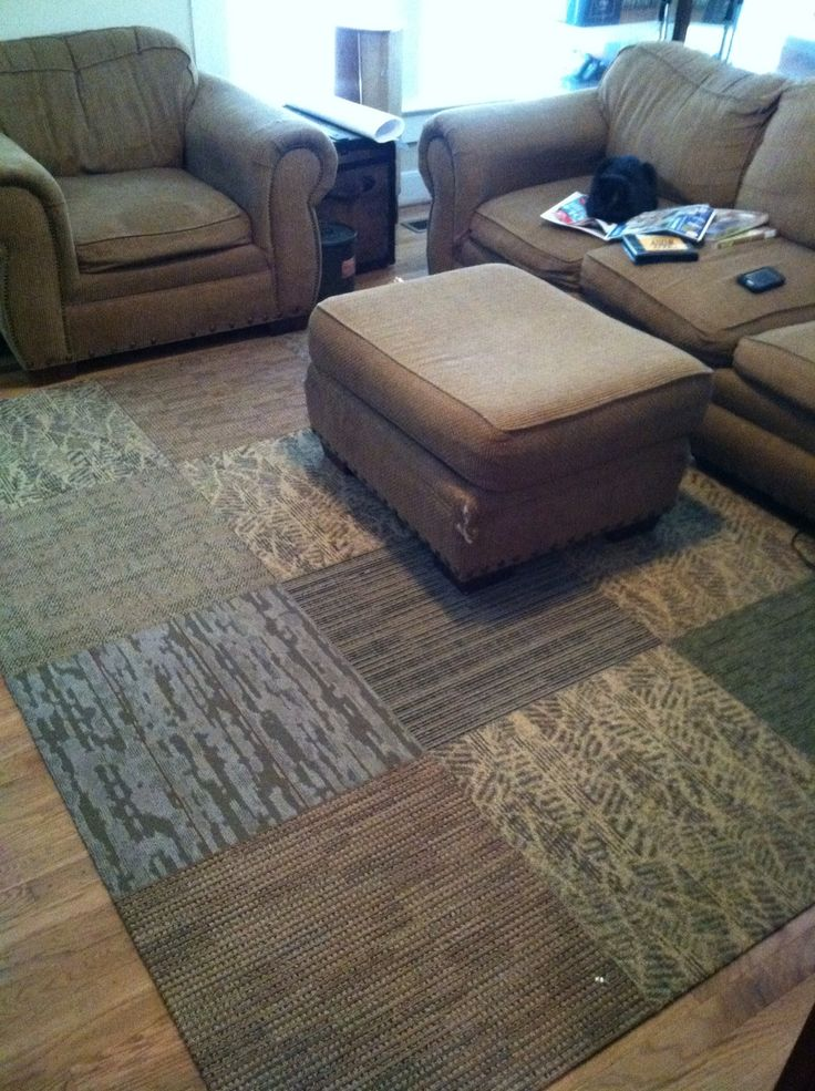 Inexpensive area rug: 12 industrial carpet tiles ($2 ea) connected with extra sticky black gorilla tape ($9). $33 for a 6'x8' rug that's nearly indestructible. Easy too!