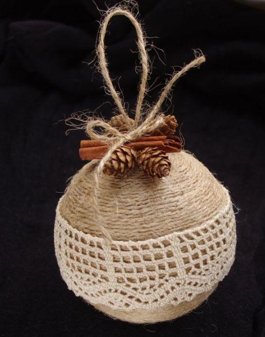 Bombka choinkowa wykonana ręcznie ze styropianowej kuli owiniętej sznurkiem jutowym, ozdobionej bawełnianą koronką, laską cynamonu i modrzewiowymi szyszkami.