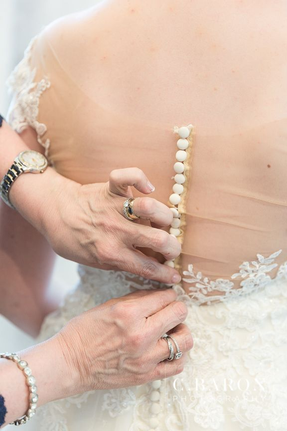 Mother Buttoning The Back Of Her Only Daughters Ivory Wedding Gown