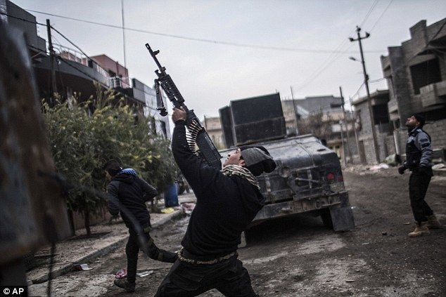An Iraqi special forces fighter shoots in the direction of a sniper in Mosul's al-Barid district