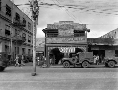 """Theater on Rizal Avenue, Manila, Philippines, featuring """"Vodavil"""". Sign on building reads """"Atomic Bomb Business Enterprises."""" People on street are unidentified. Donor: John Paxton."""