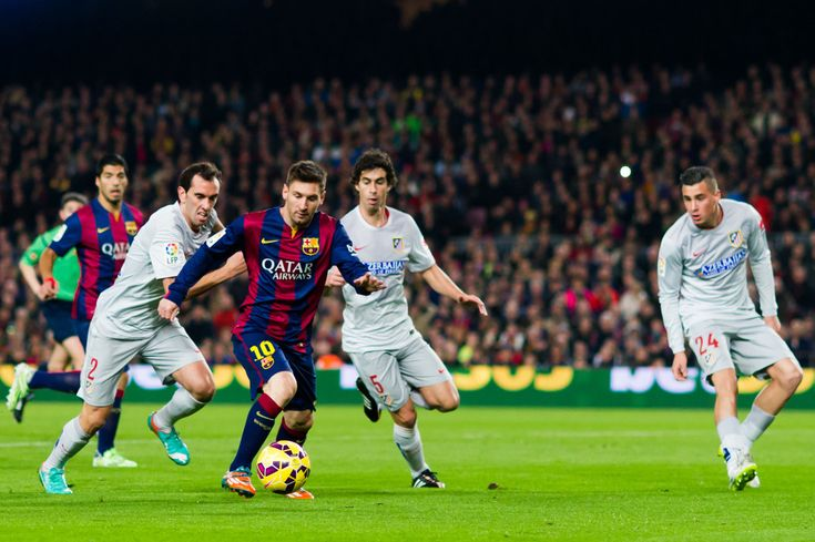 Lionel Messi of FC Barcelona plays the ball next to Diego Godin (L), Tiago Mendes (C) and Jose Maria Gimenez (R) of Club Atletico de Madrid during the La Liga match between FC Barcelona and Club Atletico de Madrid at Camp Nou on January 11, 2015 in Barcelona, Catalonia.