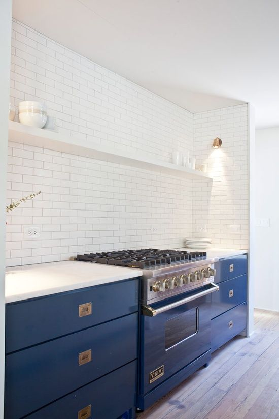 white subway tile kitchen with blue lacquer lower cabinets and brass hardware. open shelving.