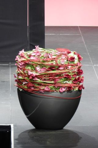 Flower pot design - created using a base of green hydrangea and then the entire design is whirlwind of entwined mini callas, grass, and Oasis Flat Cane. - David Ragg & David Denyer