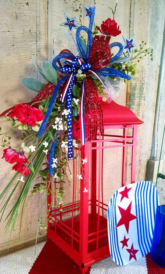 Show your pride of the USA by adding this lantern swag to your Independence Day decorations. Adding this arrangement to your favorite lantern would make a super easy and eye-catching picnic centerpiece. It would also look great on your front porch or kitchen island.  The arrangement measures 20 overall and is shown on a 20 lantern which is not included in the sale. It features red and white flowers along with silver, red and blue metal stars that sparkle! Red foil ribbon, blue deco tubing…