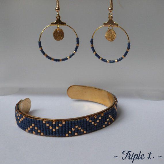 ~ DESCRIPTIF ~ Ce bracelet manchette LANA est composé dun tissage fait main avec des perles de verre Miyuki et dune manchette en laiton. Couleurs des perles : bleu marine - doré. Dimensions : 1 cm de large. ~ MATERIEL UTILISE ~ - Perles de verre japonaises Miyuki - Manchette en laiton brut  ~ ENVOI ~ Les bijoux sont envoyés en courrier suivi dans une enveloppe en papier bulle et soigneusement emballés.  ~ PRECAUTIONS DUSAGE ~ Ce bijou est fait à la main et avec soin. Il nécessite beaucoup…