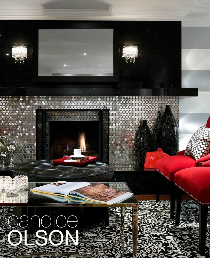 This fireplace is tiled with large-scale penny tiles in a stainless steel finish. About the size of silver dollars, the tiles have a retro Las Vegas vibe. They're made of terra-cotta with a stainless-steel cap and are attached to a mesh backing to make installation relatively easy. I used gray grout to blend them with the black quartz. #candiceolson