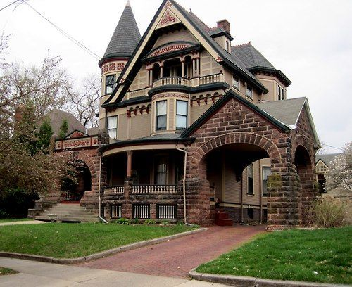 """This little beauty has some interesting aspects.  I love the brick, the rounded main entryway echoed by a rounded porch, the porte-cochère, big steeped roof and little """"royal"""" balcony, witch's hat, and some nice detail."""
