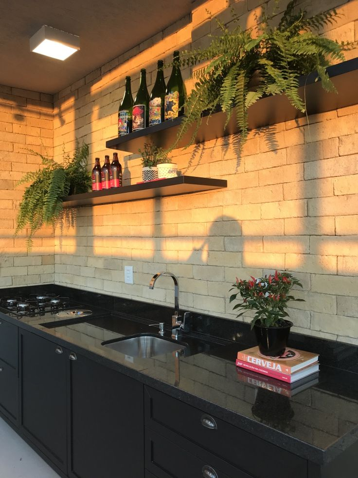 Cozinha gourmet! Na parede, revestimento da Palimanan, marcenaria em laca preta e granito preto são gabriel. Para otimizar a bancada de trabalho projetamos uma lixeira embutida em inox na própria pedra. E para decoração, samambaias que estão super em alta! #reformadecozinha #cozinha #kitchen #tijolinhos #samanbaiasnadecoracao #cozinhapreta #nordicstyle #cozinhanordica