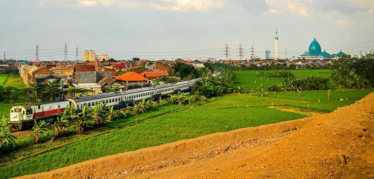 Rangkaian KA melintas di lanskap Surabaya.