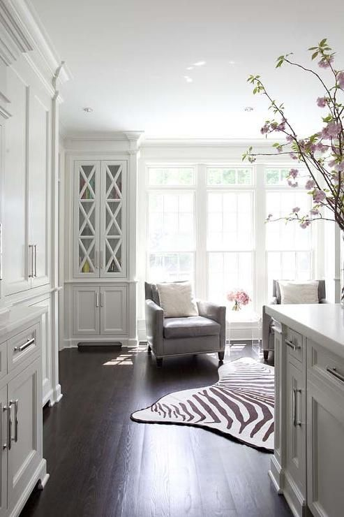KItchen sitting room is filled with a pair of gray accent chairs flanking an acrylic accent table atop a zebra cowhide rug placed in front of windows flanked by built in bookcases with glass doors.