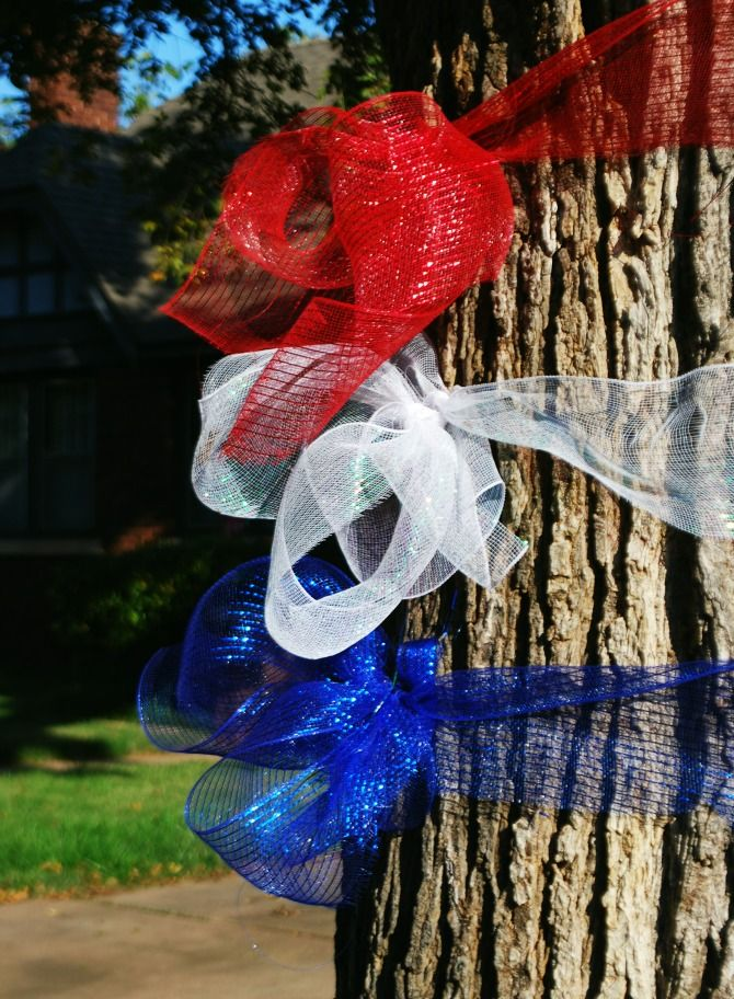 red, white and blue ribbons on a tree welcome home military