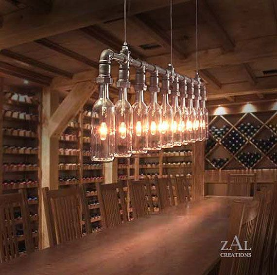"Wine Bottles suspension Lamp. Made from ten 750ml clear glass wine bottles (Bordeaux style) and 3/4 galvanized plumbing fittings. Approximate measurements: 60"" (L) x 3""(W) x 16""(T). Distance between support cables is 44 3/4"" 10 clear glass 120V; 25W incandescent (dimmable) bulbs; 250W combined wattage; 1900 Lumens combined light output."