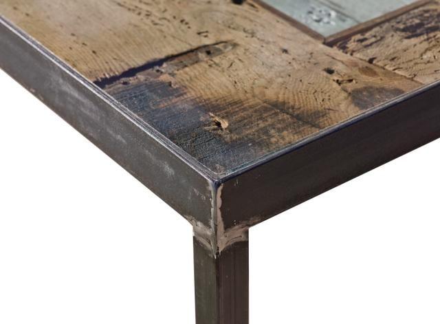 """Tavolo""""VECCHIO PORTONE"""": Realizzato con tavole di legno riciclate, lavorate ed assemblate per riprodurre la forma di un vecchio portone; la struttura è in ferro grezzo con saldature a vista il tutto appianato da una lastra di cristallo."""