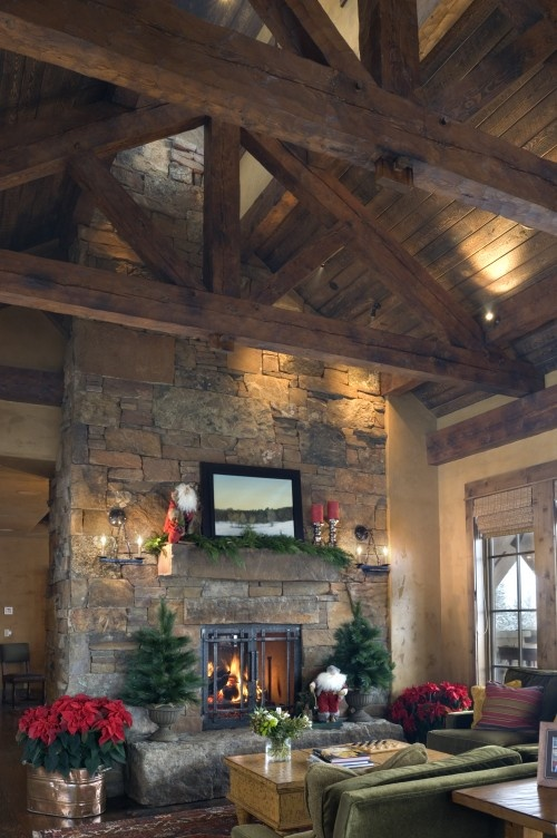 Stone wall surrounding fireplace to the ceiling cement for Exposed beam ceiling living room