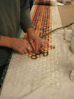 The process is to use pencil roving and wrap it around the bubbles in the bubble wrap, wetting down as you go. Paula had already worked for ca 8 hours to get this far.Permutations in Fiber: Friday's Felting Party